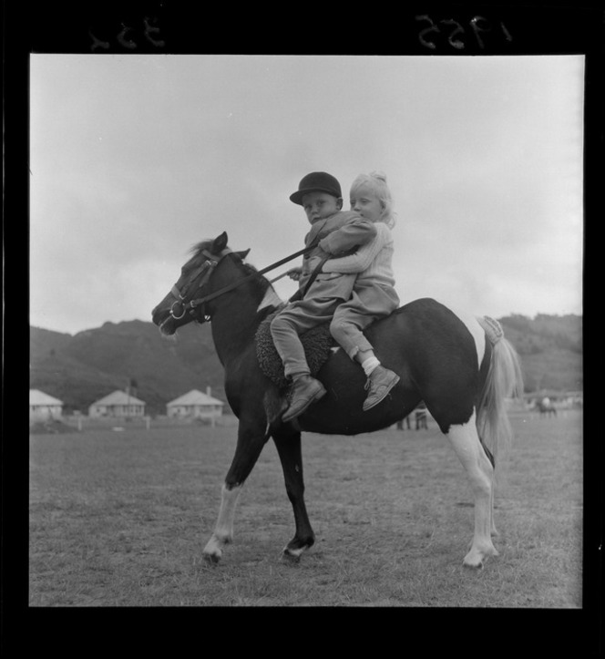 Two young children Graeme Flipp and Sue Crawston ride a pony [skewbald? piebald?] at the Upper Hutt Agricultural & Pastoral Show. Negatives of the Evening Post newspaper. Ref: EP/1955/0332-F. Alexander Turnbull Library, Wellington, New Zealand.